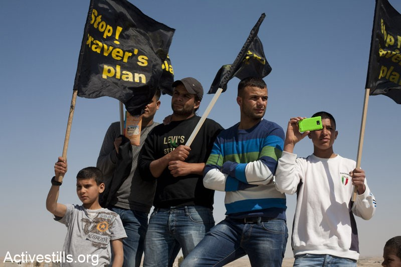 Arab-Bedouins and other activists participating in a vigil to mark Land Day in the unrecognized village of Wadi El Naam, Israel, on March 30, 2012. During the vigil the protesters held signs calling to stop Prawer Plan, approved by the Israeli government on the 11th of September, 2011. The plan will displace more than 40,000 Arab-Bedouin citizens through the destruction of most unrecognized Bedouin villages in the Negev desert (Photo: Activestills)