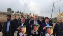 Protesters, among them Hadash chairman MK Muhammad Barakeh, holding a singe with Nelson Mandela portrait during a demonstration held in Nabi Saleh on December 7, 2013 to commemorate the killing of Mustafa Tamimi and Rushdi Tamimi by Israeli military occupation forces (Photo: Al Ittihad)