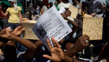 An African asylum seeker holding matzah and an alternative Passover Haggadah outside the Holot detention center (Photo: Ziv Oren)