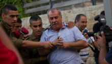 Young communists activists, dressed as Israeli soldiers hold Hadash chairman MK Mohammad Barakeh as they take part in an performance during an event against the plan to recruit to the Israeli army Arab-Palestinians, in the city of Haifa May 17, 2014 (Photo: Activestills)