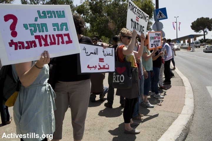 """Protest against forced feeding of Palestinian prisoners, Jerusalem, June 16, 2014. Activists and doctors take part in a demonstration, organized by Physicians for Human Rights organization, against the bill to legalize forced feeding of hunger-striking prisoners in Israel, in front of the Knesset. Sign in Hebrew reads: """"Judge, what is legal in administrative detention?"""" and in English and Arabic: """"Force Feeding = Torture."""" (Photo: Activestills)"""
