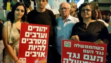 "MK Dov Khenin (second from left) during a joint Jewish-Arab demonstration in Haifa holding up a sign reading ""Jews and Arabs refuse to be enemies."" (Photo: Al Ittihad)"