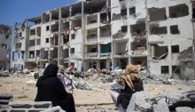 Palestinian women sit among the ruins of the Al-Nada towers after they were destroyed by Israeli strikes in Beit Hanoun, northern Gaza Strip, August 4, 2014. The towers had 90 flats. So far, Israeli attacks have killed at least 1,870 Palestinians, and injured 9,470 since the beginning of the Israeli offensive (Photo: Activestills)