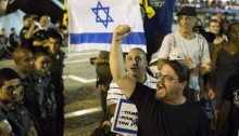 "Right-wing Israeli counter-protesters at a pro-peace demonstration in Tel Aviv. A demonstrator held a sign ""One People, One Land and One Leader"". Hundreds Left and peace activists gathered in Tel Aviv to protest Israel's attack on Gaza, despite a police decision to revoke the demonstration's permit, Rabin Square, Tel Aviv, July 9, 2014 (Photo: Activestills)"