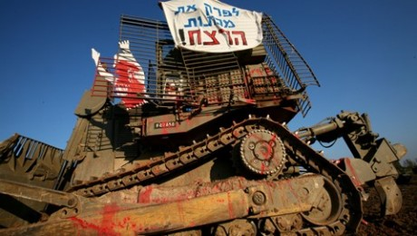 Peace demonstrators arrived on November 2006 to a military camp, between the Carni and Erez crossings, near Gaza Strip, serving as a parking lot for some 100 armored personal carriers (APC), tanks and Caterpillar's D9 armored bulldozers. While some activists climbed on the D9 bulldozers to occupy them, others displayed dummies soaked in blood and photos of Palestinian victims on and around the armored vehicles (Photo: Al Ittihad)