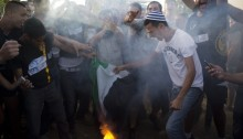 Right wing Israelis settlers burn the Palestinian flag and shout racist slogans, during an anti-Palestinian protest at the Gush Etzion junction, next to the Palestinian town of Bethlehem, following the kidnapping of three Israeli teenagers, West Bank, June 16, 2014 (Photo: Activestills)