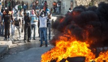 Palestinian youth has seen burning tires during demonstrations against occupation in the neighborhood of Issawia on October 24, 2014 in occupied East Jerusalem (Photo: Activestills)