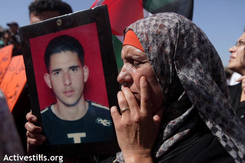 "A woman carries a picture of her imprisoned son during a demonstration in support of the Palestinian prisoners' hunger strike opposite the ""Ofer"" military court and prison, Bitunya, October 2011 (Photo: Activestills)"