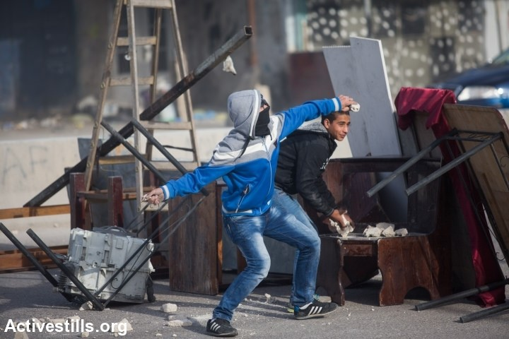 Palestinian youths throws stones during clashes with Israeli occupation forces at the Israeli Qalandia checkpoint between the West Bank city of Ramallah and Jerusalem on Friday, November 7, 2014 (Photo: Activestills)