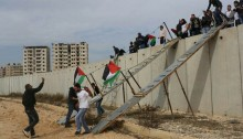 Palestinians and international activists use makeshift bridges to cross the separation wall between Qalandiya and Jerusalem, November 14, 2014. (Photo: Activestills.org)