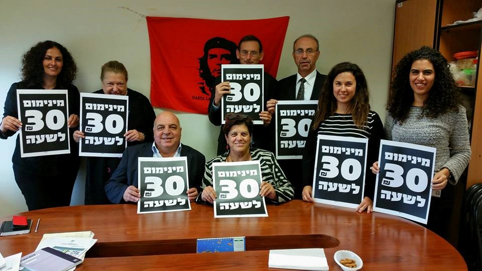 """Hadash parliamentary fraction and activists with the """"30 New Shekel per hour minimum wage"""" banner in the Knesset (Photo: Hadash)"""