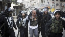 """Israeli policemen arrest a Palestinian as bulldozers of the Israeli authorities destroy Palestinian owned shops in the Shuafat refugee camp in occupied East Jerusalem, December 3, 2014. The Israeli authorities, under the supervision of Israeli forces, destroyed Palestinian owned shops """"that were built without a permit,"""" clearing space for a new parking lot for the Shuafat checkpoint (Photo: Activestills)"""