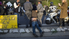 Israeli police drag away a protester as activists block the Ayalon Highway during the eviction of the 8 families from their homes in the Givat Amal neighborhood, Tel Aviv, December 29, 2014.
