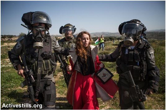 Israeli border policemen arrest a Hadash activist protester during the demonstration marking ten years of popular struggle against in the West Bank village Bil'in, February 27, 2015.