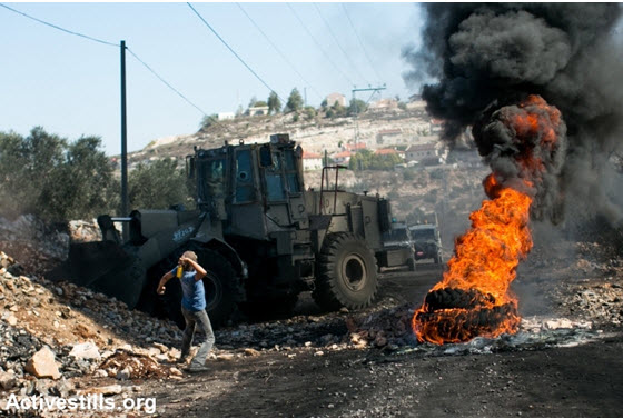 A demonstrator hurls a stone at an Israeli army bulldozer during the weekly demonstration against the occupation in the West Bank village of Kafr Qaddum, October 25, 2013.