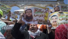 Palestinian worshippers at the Al-Aqsa Mosque compound in Jerusalem protest, calling for the release of prisoners during the first Friday of the holy month of Ramadan, Friday, June 19, 2015; among the prisoners whose release is demanded, Khader Adnan pictured in the foreground poster.