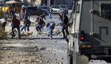 Palestinians from the al-Jalazone Refugee Camp clash with Israeli forces at the entrance the Jewish-only settlement of Beit El near Ramallah on Oct. 24, 2014.