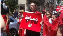"MK Dov Khenin during this past year's May Day parade in Tel Aviv with the Hadash banner calling for ""Equality"" in Hebrew and Arabic"