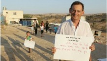 "Hadash MK Dov Khenin (Joint List) during a demonstration against eviction of the Arab-Bedouin village of Atir-Umm al-Hiran. The sign held by MK Khenin reads (in print): ""I oppose the destruction of Umm al-Hiran because:"" and continues in handwriting: ""every child deserves a home and the Negev will only have a real future if there will be true equality here."""