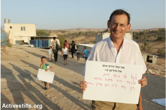"""Hadash MK Dov Khenin (Joint List) during a demonstration against eviction of the Arab-Bedouin village of Atir-Umm al-Hiran. The sign held by MK Khenin reads (in print): """"I oppose the destruction of Umm al-Hiran because:"""" and continues in handwriting: """"every child deserves a home and the Negev will only have a real future if there will be true equality here."""""""