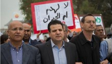 "Hadash MKs from the Joint List, Ayman Odeh (center) and Dov Khenin (right), taking part in the march to the Be'er Sheva District Courthouse, to protest against the planned demolition of Umm al-Hiran and Atir, March 3, 2016. The sign in the background reads in Arabic: ""No to the destruction of Umm al-Hiran."""