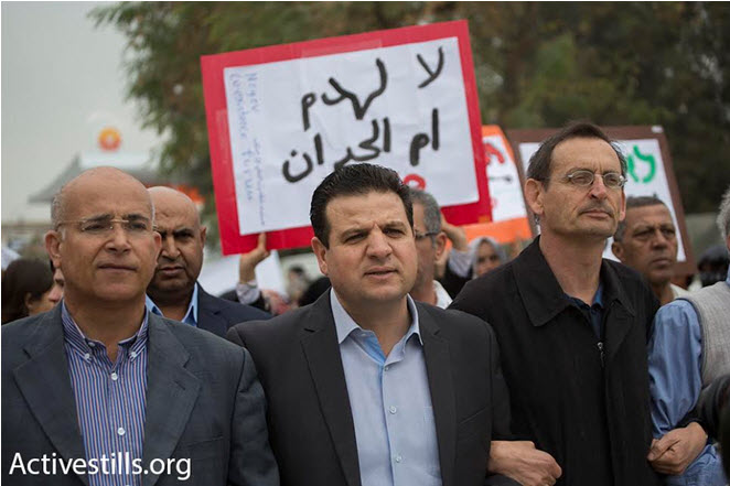 """Hadash MKs from the Joint List, Ayman Odeh (center) and Dov Khenin (right), taking part in the march to the Be'er Sheva District Courthouse, to protest against the planned demolition of Umm al-Hiran and Atir, March 3, 2016. The sign in the background reads in Arabic: """"No to the destruction of Umm al-Hiran."""""""