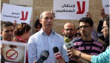 "Palestinian journalist Omar Nazzal who was arrested by Israel authorities on April 23. The signs in Arabic, from an earlier protest, read ""No to the arrest of journalists."""