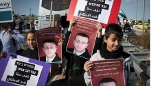 Palestinians and Israelis holding posters of Muhammad al-Qiq during a joint protest at the Tunnel Checkpoint, south of Jerusalem, February 5, 2016