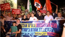 "MK Dov Khenin (third from right) holds a sign aloft: ""Building an opposition; building hope,"" in Saturday night's mass demonstration in Tel-Aviv"