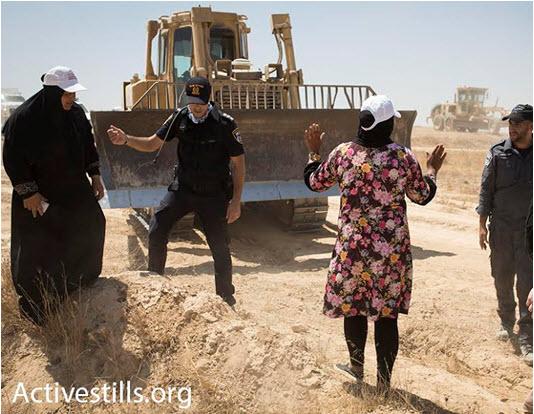 An Arab-Bedouin woman attempts to block a bulldozer in the unrecognized village of Al-Araqib, Negev Desert, July 24, 2016.