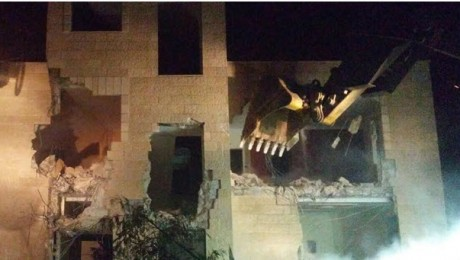 Secured by armed Israeli forces, a bulldozer destroys one of a 20 Palestinian homes demolished in occupied East Jerusalem on Monday night, July 25.
