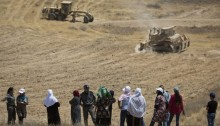 Arab-Bedouin women watch as bulldozers of the Jewish National Fund (JNF) plow private lands belonging to the unrecognized village of Al Araqib, July 20, 2016. During the last six years, Al-Araqib has been demolished more than one hundred times.