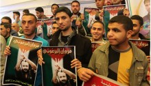 Palestinians in Gaza hold aloft posters in support of imprisoned Palestinian leader Marwan Barghouti during a sit-in at the offices of the International Committee of the Red Cross.