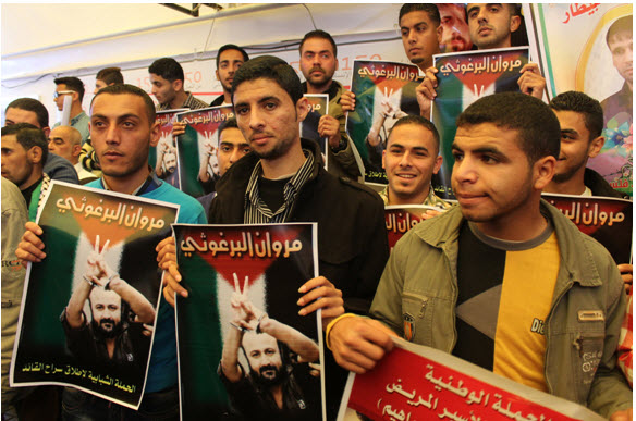 Palestinians in Gaza hold aloft posters in support of imprisoned Palestinian leader Marwan Barghouti during a demonstration at the offices of the International Committee of the Red Cross in their city, besieged by Israel.