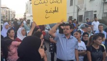"Joint List chairman MK Ayman Odeh during the demonstration in Lod against ""honor killings,"" September 26; the placard held aloft reads: ""Violence tears apart society."""