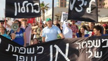 """A demonstration in Haifa against air pollution from privatized Oil Refineries group. The banner reads: """"My family OR the Ofer Family - We're escalating the struggle for the health of the residents of the Haifa Bay."""""""
