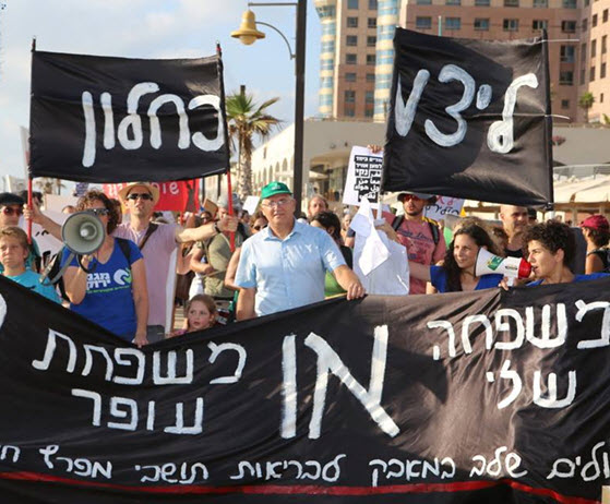 "A demonstration in Haifa against air pollution from privatized Oil Refineries group. The banner reads: ""My family OR the Ofer Family - We're escalating the struggle for the health of the residents of the Haifa Bay."""