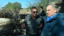 Prime Minister Benjamin Netanyahu with a Border Police officer at the scene of one of the fires after it was extinguished