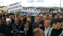 """Demonstrators in Arara on Saturday, January 21. The sign to the left reads: """"House demolitions and the killing of Arab civilians are crimes against humanity."""" The sign in the center reads: """"Bibi = Daesh; al-Kaeean = Humanity."""""""