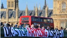 "Demonstrators on a bridge spanning the Thames next to the British Houses of Parliament call to ""Stop Arming Israel."""