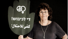 "Edna Zaretzky Toledano, one of the founders of Women in Black and former Hadash member of the Haifa City Council, holds a placard reading ""Enough Occupation!"" in Hebrew and Arabic."