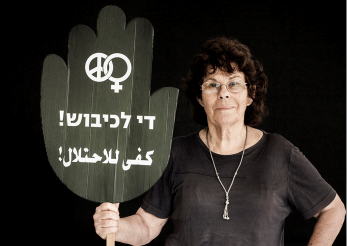 """Edna Zaretzky Toledano, one of the founders of Women in Black and former Hadash member of the Haifa City Council, holds a placard reading """"Enough Occupation!"""" in Hebrew and Arabic."""