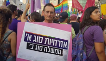 "MK Dov Khenin during the protest held in Tel Aviv, on Thursday evening July 20; the sign he's carrying reads: ""First Class Citizenship, Second Class Government."""