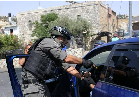 An Israeli police officer violently confronts a Palestinian resident in occupied East Jerusalem, July 21, 2017.