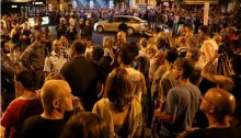 Demonstrators gather outside of the Petah Tikva police station on Saturday night, August 19.