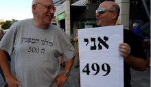 "Two of the some 2,000 protestors who turned out on Saturday evening in Petah Tikva, make light of the supposed limit of 500 set for the event: ""I'm demonstrator number 499"" declares one of them in the sign he's holding, and to the left the grey t-shirt reads: ""All of us are demonstrator number 500."""