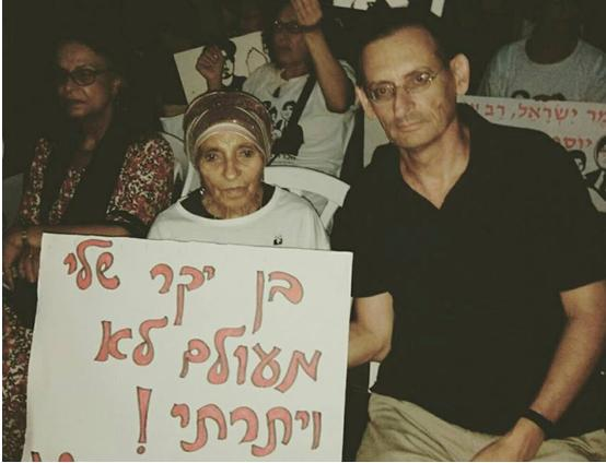 "Shoshanna Nachshon and MK Dov Khenin during the protest demanding the state admit to the abduction of the children of immigrants from Yemen, the Middle East and the Balkans, on Monday, September 25; the sign reads ""My dear son, I never gave up!"""
