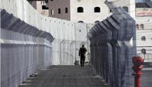 A Palestinian resident of occupied East Jerusalem walks through a checkpoint that separates the entirely walled-off neighborhood of the Shuafat Refugee Camp from the rest of Jerusalem.