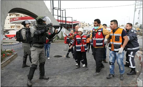 An Israeli Border Policeman threatens Palestinian medics and journalists with point blank death during a protest at the Beit El junction, occupied West Bank, December 22, 2017.