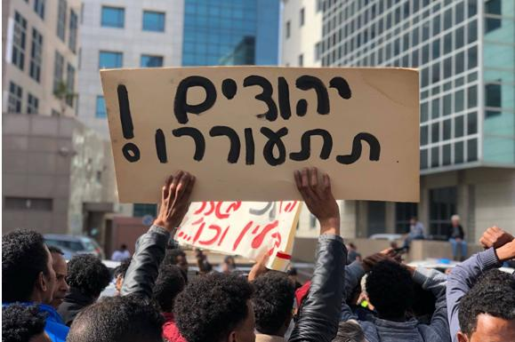 "2,000 asylum seekers and Israeli activists gathered on Monday, January 22, outside of the Rwandan embassy in Herzliya to protest the reported agreement between the governments of Israel and Rewanda to deport asylum seekers to the latter country. The raised placard reads ""Jews, wake up!"""